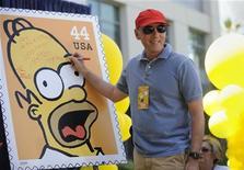 """<p>Dan Castellaneta, que faz a voz de Homer Simpson em inglês, assina pôster de lançamento de novos selos dos """"Simpsons"""" em Los Angeles em 2009. O fã de cerveja e comedor de rosquinhas recheadas Homer Simpson foi apontado como o maior personagem criado para a televisão e o cinema nos últimos 20 anos. REUTERS/Phil McCarten</p>"""