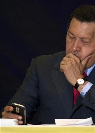 Venezuela's President Hugo Chavez looks at his Blackberry while attending a ceremony at the headquarters of the state-run oil company PDVSA in Caracas May 12, 2010. REUTERS/Carlos Garcia Rawlins