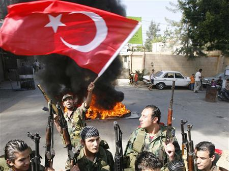 A Palestinian fighter from the Democratic Front for the Liberation of Palestine (DFLP) waves a Turkish flag in front of burning tyres at Ain el-Hilweh refugee camp, southern Lebanon June 1, 2010, during an anti-Israel protest after the storming of a Turkish aid ship bound for Gaza by Israeli marines on Monday. REUTERS/Ali Hashisho