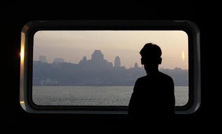 A man looks through a window as smoke covers the skyline of Quebec City May 30, 2010. REUTERS/Mathieu Belanger