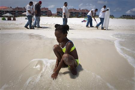 Aunye Kay of St. Louis, Missouri, plays in the water as contract workers clean oil globs from the Deepwater Horizon oil spill blanket a beach in Pensacola Beach, Florida June 4, 2010. REUTERS/Lee Celano