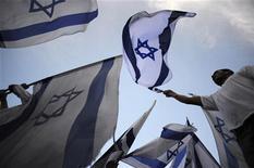 <p>Израилитяне размахивают флагами страны во время митингов солидарности с действиями правительства по отношению к турецким кораблям в Ашкелоне 6 июня 2010 года. Израиль ответил отказом на предложение генерального секретаря ООН Пан Ги Муна о начале международного расследования инцидента с гуманитарной флотилией, направлявшейся в сектор Газа. REUTERS/Amir Cohen</p>