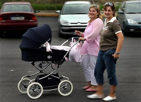Toni Melendez (L) and her partner Maria Angeles Zucilla take their baby for a walk as they talk to the media in the southern Spanish town of Algeciras October 17, 2006. REUTERS/Anton Meres