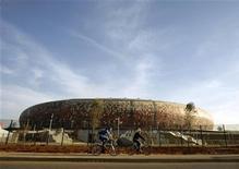 """<p>Люди проезжают на велосипедах мимо стадиона """"Соккер Сити"""" в Йоханнесбурге 2 июня 2010 года. Перед началом чемпионата мира по футболу в ЮАР Google сделал новые снимки стадионов, на которых пройдут матчи турнира, а также их 3D-макеты, говорится в сообщении на официальном блоге Google Россия. REUTERS/Henry Romero</p>"""