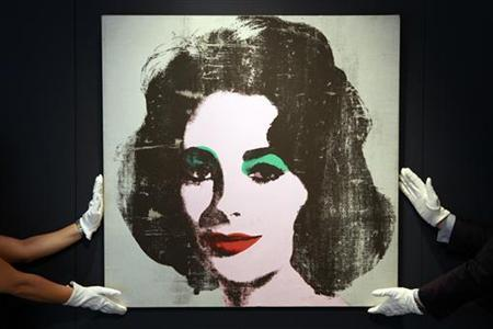 Employees pose for photographers with the 1963 ''Silver Liz'' portrait of actress Elizabeth Taylor by late artist Andy Warhol, unseen in over 20 years, at Christie's auction house in London June 8, 2010. Christie's estimates the painting will fetch 6 to 8 million pounds (8.7 to 11.6 million US dollars) at its auction on June 30. REUTERS/Stefan Wermuth