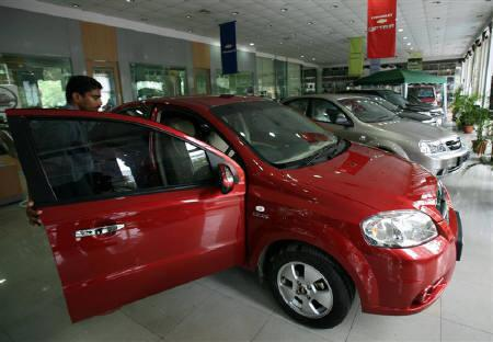 A worker opens the door of a car at a showroom in Mumbai August 3, 2006.  Car sales in India posted their best May ever, rising by almost a third from a year ago, an industry body said on Wednesday, as rising incomes and a rapidly expanding economy offset the impact of price increases. REUTERS/Punit Paranjpe/Files