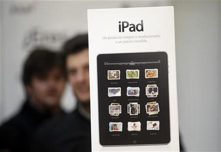 Visitors walk past a poster advertising the new iPad at an Apple retail store in Madrid May 28, 2010. REUTERS/Susana Vera