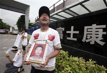 Ma Zishan (C) cries as he carries a portrait of his son Ma Xiangqian outside a Foxconn factory in the township of Longhua, Guangdong province May 29, 2010. REUTERS/Stringer