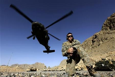 A U.S. Army soldier with the 2nd Battalion, 508th Parachute Infantry Regiment, and part of the 82nd Airborne Division, takes cover as a Black Hawk chopper takes off from a U.S. military base in Arghandab valley in this May 14, 2010 file photo. REUTERS/Yannis Behrakis