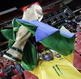 <p>Torcedor brasileiro ergue réplica de taça na partida contra a Coreia do Norte em Johanesburgo. REUTERS/Kai Pfaffenbach</p>