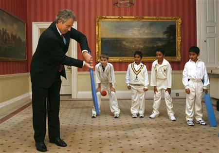 Then British Prime Minister Tony Blair plays cricket with children from the London Sports Clubs inside 10 Downing Street in London November 22, 2006. REUTERS/Alessia Pierdomenico