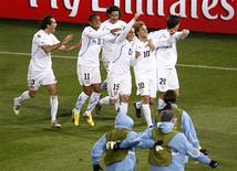 <p>Diego Fórlan e jogadores uruguaios comemoram gol em partida contra a África do Sul: para treinador, time sul-americano precisa jogar com mais tranquilidade. REUTERS/Brian Snyder</p>