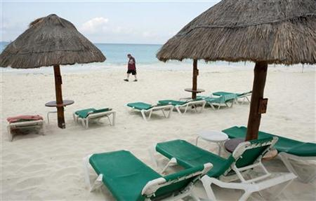 A tourist walks past empty beach chairs in Cancun, April 13, 2010. REUTERS/Gerardo Garcia