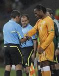 <p>Árbitro Jorge Larrionda, do Uruguai, checa o braço do atacante Didier Drogba, da Costa do Marfim, antes do jogador entrar em campo em 15 de junho. REUTERS/Denis Balibouse</p>