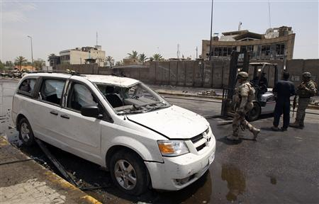 Iraqi soldiers inspect the site of a bomb attack in Baghdad June 20, 2010. Suicide car bombers attacked the Trade Bank of Iraq on Sunday, killing at least 26 people, an Interior Ministry source said. REUTERS/Saad Shalash