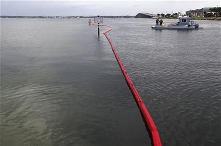 Escambia County Oil Spill Response workers set oil containment booms near the bridge to Pensacola Beach, Florida June 5, 2010, to protect an area from the Deepwater Horizon oil spill. REUTERS/Colin Hackley