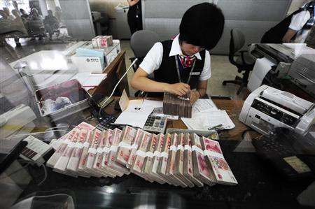 An clerk counts yuan banknotes at a bank in Hefei, Anhui province, June 20, 2010. China will gradually make the yuan's exchange rate more flexible, the central bank said on Saturday, indicating that it was ready to break a 23-month-old U.S. dollar peg. REUTERS/Stringer