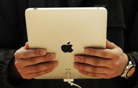 A customer hold the new iPad tablet computer at its UK launch at an Apple store in central London May 28, 2010. REUTERS/Luke MacGregor