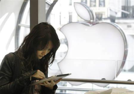 A customer tests the iPad tablet computer in an Apple store in central London in this May 28, 2010 file photo. Apple has sold 3 million iPads in less than three months, a faster-than-expected pace that boosted its stock days before the company's newest iPhone hits store shelves. REUTERS/Luke MacGregor/Files