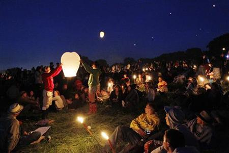 Festival-goers sit around candles and set of paper lanterns at the stone circle at the Glastonbury Festival 2010 in south west England, June 23, 2010. REUTERS/Luke MacGregor