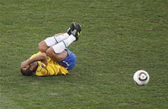 <p>Felipe Melo deita no gramado após ser atingido em jogada com o português Pepe: dificilmente o jogador estará nas oitavas. REUTERS/Paul Hanna</p>