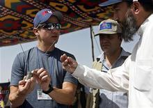 """<p>Jeremy Renner (esq), astro do filme vencedor de Oscar """"Guerra ao Terror"""" fala com especialistas em desativar bombas em Bagram, ao norte de Cabul. Renner enfrentou um campo minado real no Afeganistão, para chamar a atenção para o trabalho incansável de desativação de minas que continuam a matar e mutilar pessoas. 27/06/2010 REUTERS/Jonathon Burch</p>"""