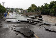 <p>Дорога в Сан-Сальвадоре, разрушенная в результате тропического шторма Алекс, 28 июня 2010 года. Тропический шторм Алекс достигнет ураганной силы во вторник, что может вынудить нефтяную компанию BP Plc приостановить попытки увеличить количество собираемой в Мексиканском заливе нефти. REUTERS/Luis Galdamez</p>