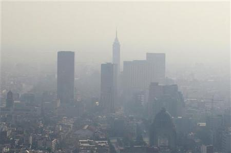 Buildings stand shrouded in smog in Mexico City December 11, 2009. REUTERS/Daniel Aguilar