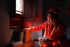 "<p>""Living Goddess"" Kumari Chanira Bajracharya looks for a book while studying at her residence at Patan in Nepal March 11, 2010. REUTERS/Shruti Shrestha</p>"