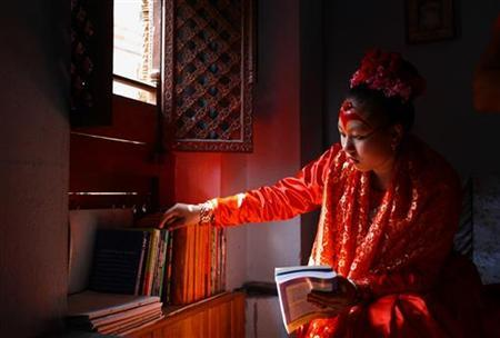 ''Living Goddess'' Kumari Chanira Bajracharya looks for a book while studying at her residence at Patan in Nepal March 11, 2010. REUTERS/Shruti Shrestha