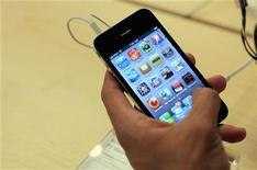 <p>Cliente manuseia iPhone em Nova York. A Apple afirmou que seus iPhones exageram a força do sinal da rede sem fio e prometeu corrigir a falha nas próximas semanas. Usuários vinham reclamando sobre o design da antena do telefone.24/06/2010.REUTERS/Eric Thayer</p>