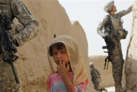 An Afghan girl passes by U.S. soldiers with C Troop 1-71 CAV during their patrol in the village of Gorgan in Dand district, south of Kandahar, June 28, 2010. REUTERS/Denis Sinyakov