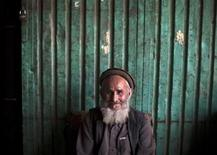 <p>An Afghan watchman smiles at the camera as he sits outside a shop at a market in Kabul May 26, 2010. REUTERS/Ahmad Masood</p>