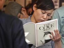 "<p>Una mujer lee un folleto de la película ""The Cove"" en una sala de cine en Tokio, jul 3 2010. REUTERS/Issei Kato (JAPAN)</p>"
