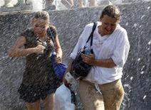 <p>Люди проходят мимо фонтана в центре Москвы 25 июня 2010 года. На этой неделе Москву немного освежат дожди, однако столбики термометров все равно останутся на отметке около плюс 30 градусов. REUTERS/Sergei Karpukhin</p>