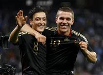 <p>Mesut Ozil, de origem polonesa (esq), e Lukas Podolski, de ascendência turca, comemoram vitória da seleção alemã contra a Argentina nas quartas de final da Copa do Mundo. Os imigrantes ajudaram a Alemanha a formar um time forte no Mundial, disse o ministro dos Esportes alemão, Thomas de Maiziere. 03/07/2010 REUTERS/Kai Pfaffenbach</p>