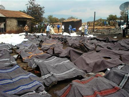 The charred remains of corpses lie under blankets near rescue workers in Sange, eastern Congo after an oil tanker crashed and exploded, killing hundreds in a fireball, July 3, 2010. REUTERS/Fiston Ngoma/United Nations/Handout