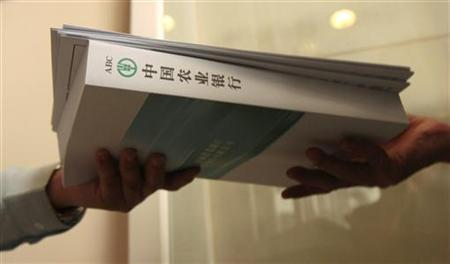 A potential investor collects application forms and a Agricultural Bank of China prospectus during its initial public offering (IPO) in Hong Kong June 30, 2010. REUTERS/Tyrone Siu