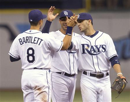 Tampa Bay Rays' Jason Bartlett (L) celebrates with teammates Carlos Pena (C) and Sean Rodriguez after defeating the Boston Red Sox during their MLB American League baseball game in St. Petersburg, Florida July 5, 2010. REUTERS/Scott Audette