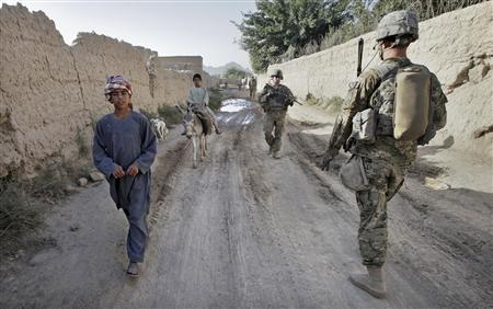 Local boys walk past U.S. Army soldiers from Alpha Company, 2-508 Parachute Infantry Regiment, 4th Brigade Combat Team, as they conduct a morning patrol through the village of Kowall in Arghandab District, north of Kandahar July 11, 2010. REUTERS/Bob Strong