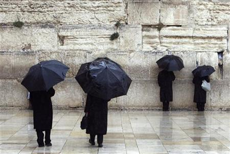 Jewish worshippers hold umbrellas on a rainy day at the Western Wall, Judaism's holiest prayer site, in Jerusalem's Old City February 3, 2010. REUTERS/Ronen Zvulun