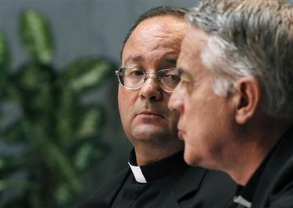 Monsignor Charles Scicula (L), a Vatican doctrinal official, watches as Vatican's spokesman Father Federico Lombardi speaks during a news conference in the Holy See press office at the Vatican July 15, 2010. REUTERS/Alessandro Bianchi