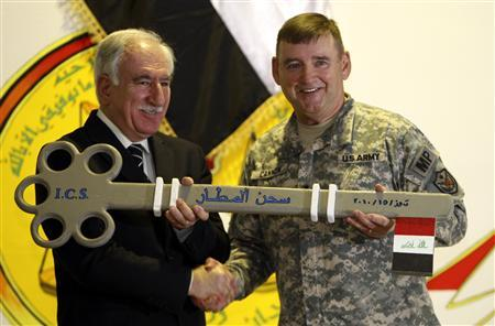 U.S. Major General Jerry Cannon (R) dedicates a giant key to Iraq's Justice Minister Dara Noor-Eldeen as a symbolic gesture during a ceremony marking the transfer of Camp Cropper, the last U.S. detention centre in Iraq, to the Iraqi government in Baghdad July 15, 2010. REUTERS/Saad Shalash