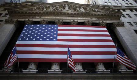 U.S. flags hang on the facade of the New York Stock Exchange October 8, 2009.  REUTERS/Chip East/Files