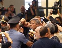 <p>George Clooney (centro) é rodeado por multidão ao sair de tribunal de Milão.C looney prestou depoimento nesta sexta-feira contra três pessoas acusadas de usar seu nome para promover uma marca de roupas em Milão. 16/07/2010 REUTERS/Alessandro Garofalo</p>