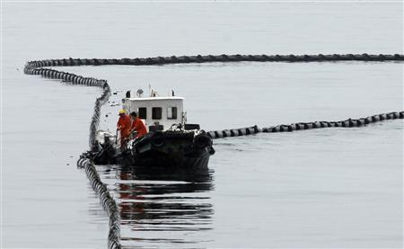 A vessel cleans up crude oil in the sea near Dalian, Liaoning province July 19, 2010. REUTERS/China Daily
