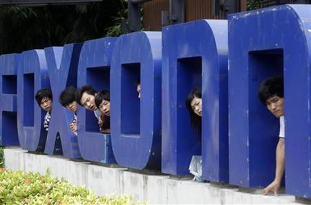 Workers look on from a Foxconn logo near the gate of a Foxconn factory in the township of Longhua, Guangdong province May 29, 2010. REUTERS/Stringer