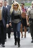 <p>Atriz Lindsay Lohan chega a um tribunal de Beverly Hills ao lado da promotora Shawn Chapman Holley (atrás) para iniciar a cumprir sentença de 90 dias de prisão por quebra de condicional. 20/07/2010 REUTERS/Danny Moloshok</p>