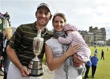 <p>Louis Oosthuizen of South Africa poses with his wife Nel-Mare and daughter Jana after winning the British Open golf championship on the Old Course in St. Andrews, Scotland, July 18, 2010. REUTERS/Christer Hogland</p>
