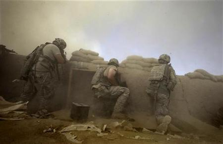 U.S. Army soldiers with the 1-320 Field Artillery Regiment, 101st Airborne Division, are covered in dust as a Chinook helicopter lands outside their base during a firefight at Combat Outpost Nolen in the Arghandab Valley north of Kandahar, July 19, 2010. REUTERS/Bob Strong